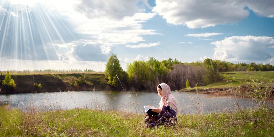 Мусульманка, читающая Коран возле озера