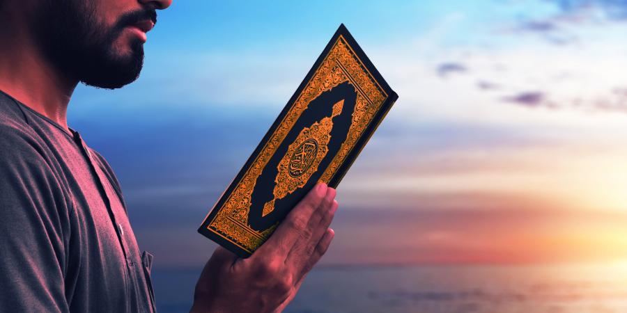 Мужчина, читающий Коран возле моря