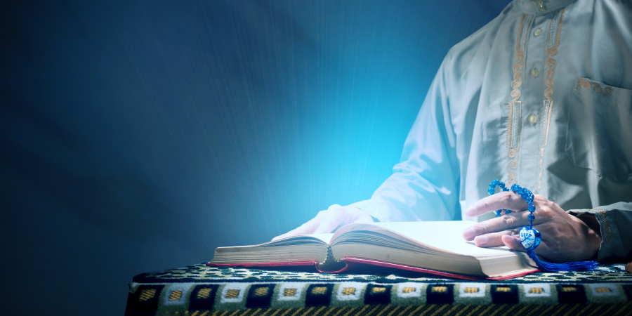 Мужчина, читающий светящийся Коран