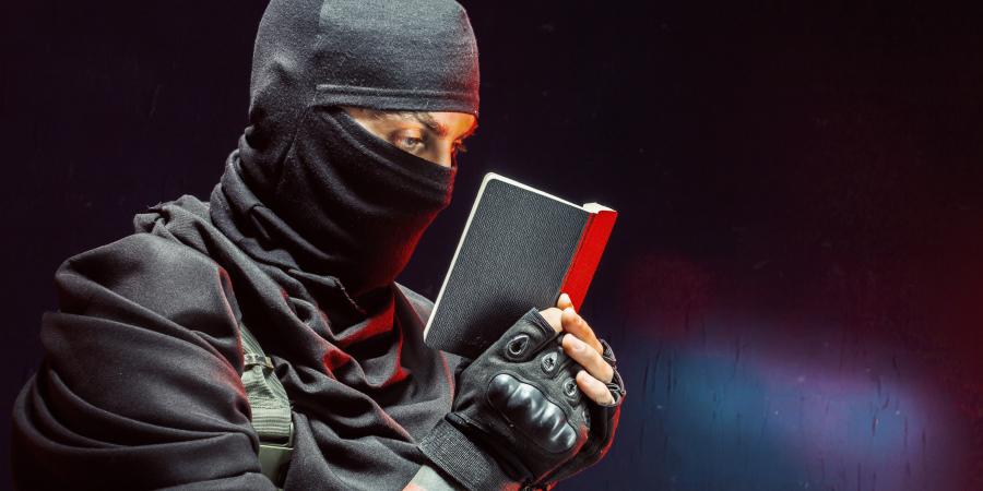 Мужчина в маске, читающий блокнот
