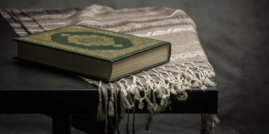 Зелёный Коран на деревянном столике