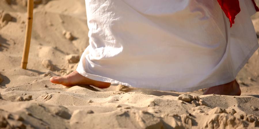 Мужчина с посохом в белых одеждах, ступающий по песку