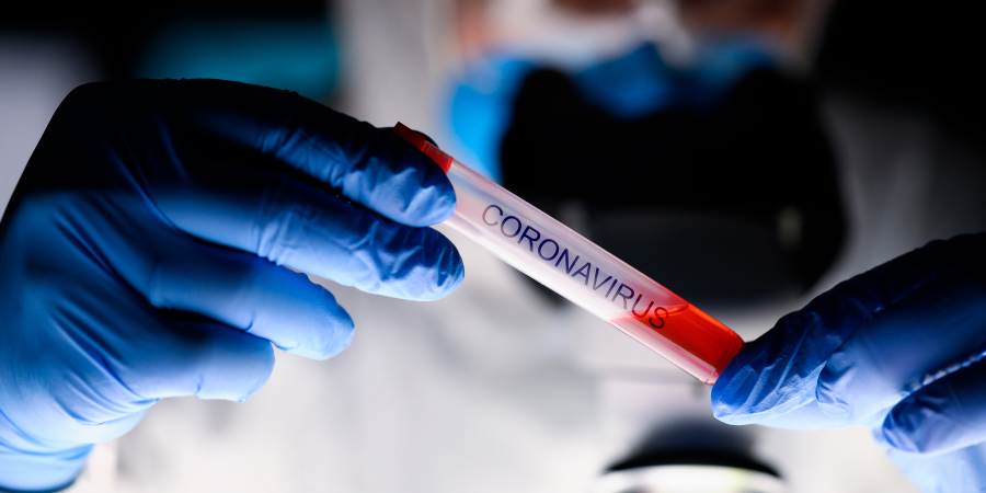 Врач, держащий в перчатках пробирку с коронавирусом