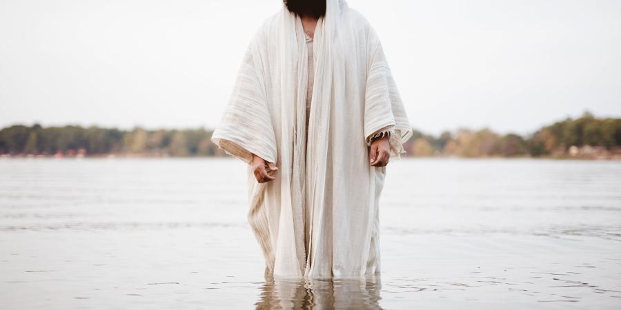 Человек в белом одеянии, стоящий в воде