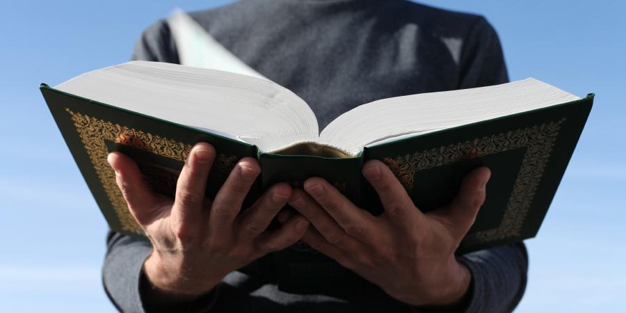 Мужчина, держащий в руках открытый Коран
