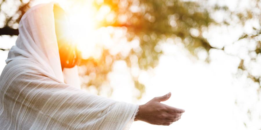 Мужчина в белом одеянии с вытянутой рукой