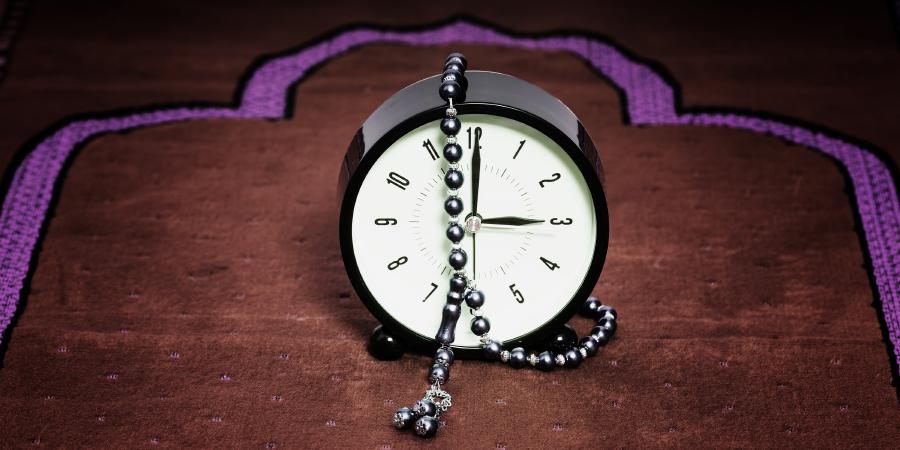 Часы и чётки на молитвенном коврике