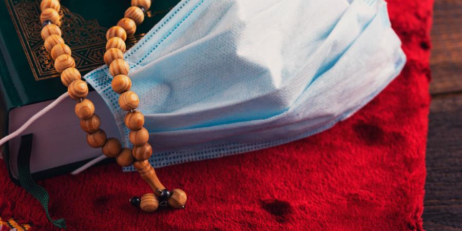 Чётки, медицинская маска и Коран на молитвенном коврике