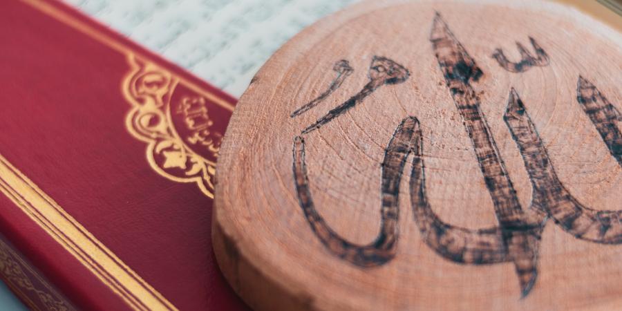 Красный Коран и кусок дерева с именем Аллаха
