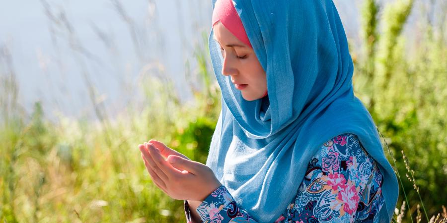 Мусульманка в синем хиджабе, молящаяся на природе