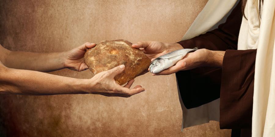 Мужчина, передающий другому хлеб и рыбу