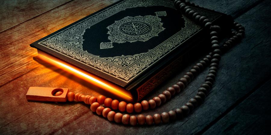 Чётки и светящийся Коран на деревянном столе
