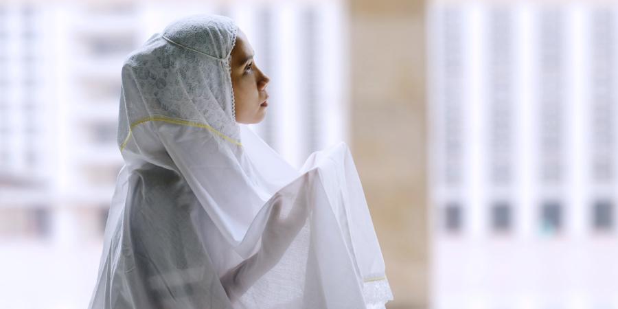 Мусульманка в белом хиджабе во время молитвы