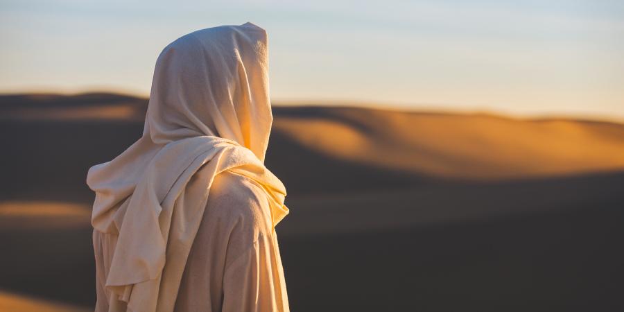 Человек в белой одежде, стоящий посреди пустыни