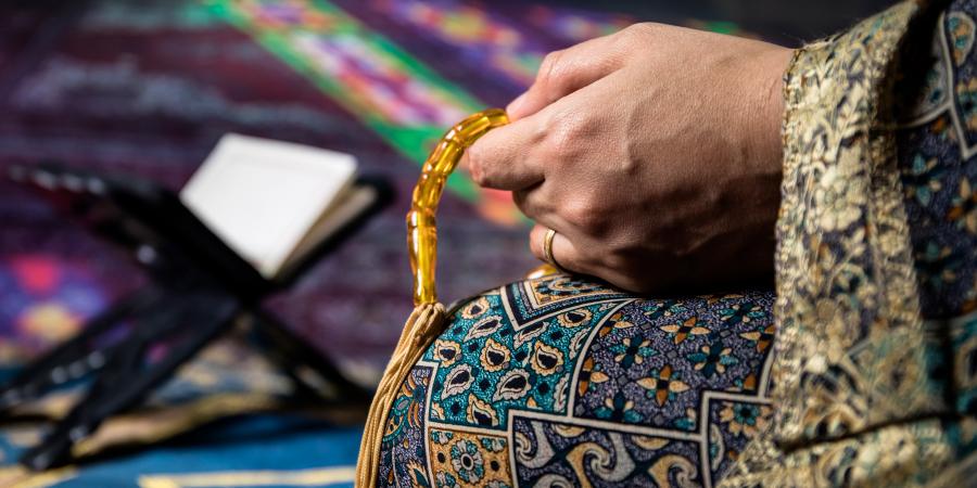 Женщина, перебирающая чётки перед открытым Кораном в мечети