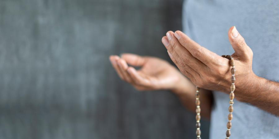 Мужчина в белой футболке, молящийся с чётками на руке