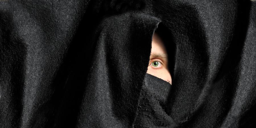 Мужчина, выглядывающий одним глазом из-под чёрной ткани